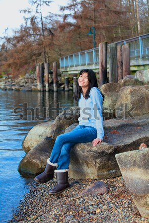 Young teen girl relaxing on large boulder along lake shore, smil Stock photo © jarenwicklund