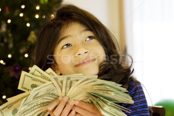 Little girl holding up large amount of cash at Christmas Stock photo © jarenwicklund