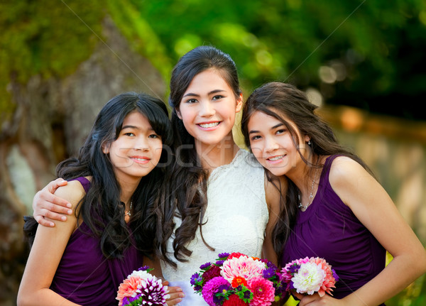 Bride with her two bridesmaid holding bouquet outdoors together Stock photo © jarenwicklund