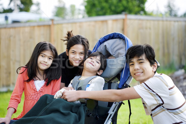 Three children surrounding a small disabled child in wheelchair Stock photo © jarenwicklund