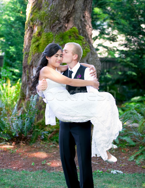 Caucasian groom carrying his biracial bride outdoors, with a kis Stock photo © jarenwicklund