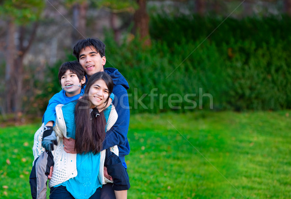Disabled biracial child riding piggy back on his sister, family  Stock photo © jarenwicklund