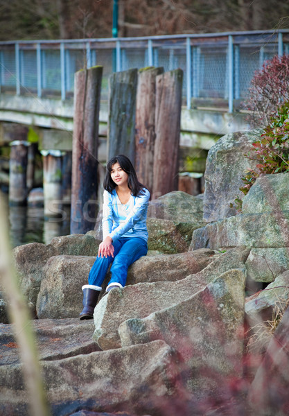 Young teen girl sitting on large boulders along lake shore, look Stock photo © jarenwicklund