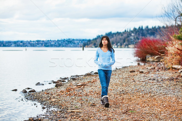 Young teen girl walking along rocky shoreline of lake in early s Stock photo © jarenwicklund