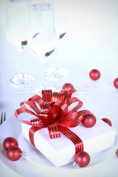 White present with red ribbons on a dinner plate, christmas them Stock photo © jarenwicklund