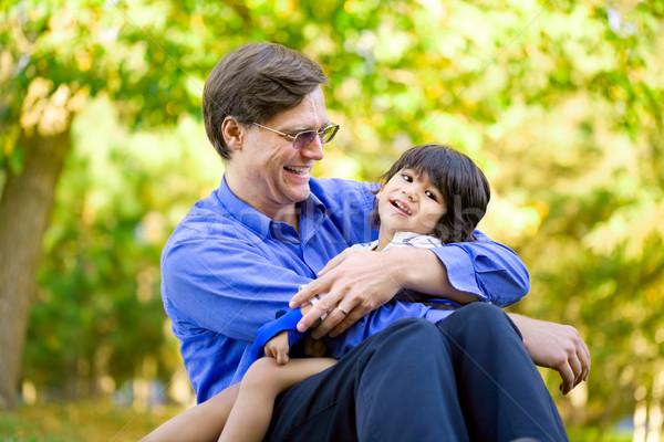 Businessman holding his disabled son on grass Stock photo © jarenwicklund