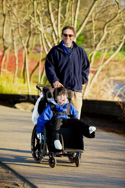 Father walking with disabled son in wheelchair Stock photo © jarenwicklund