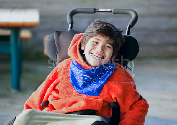 Handsome, happy biracial eight year old boy smiling in wheelchai Stock photo © jarenwicklund