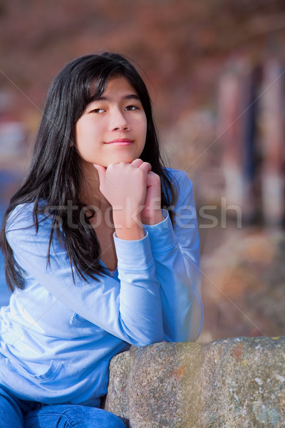 Young teen biracial girl quietly resting elbows on rock along la Stock photo © jarenwicklund