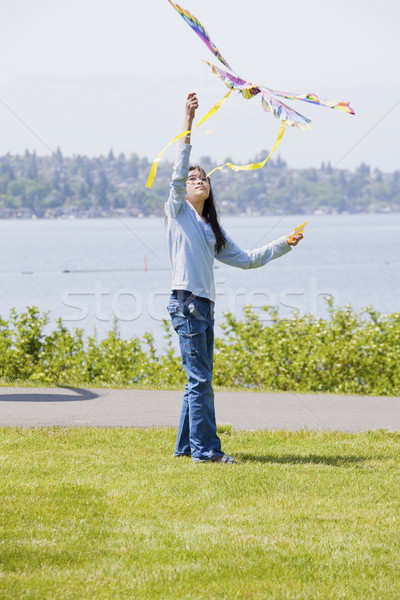 Biracial asian girl flying kite by the lake Stock photo © jarenwicklund