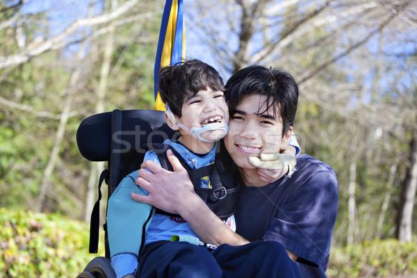 Kicsi mozgássérült fiú tolószék ölel idősebb Stock fotó © jarenwicklund