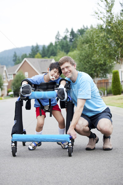 Father kneeling next to disabled son standing in walker Stock photo © jarenwicklund