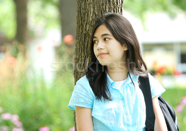Young teen girl standing with backpack by tree, smiling. Stock photo © jarenwicklund