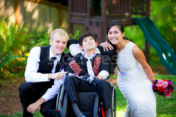Biracial bride and groom with her little disabled brother in whe Stock photo © jarenwicklund