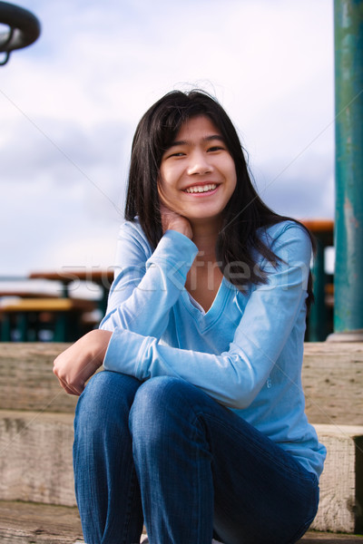 Young teen girl sitting on wooden steps outdoors on overcast clo Stock photo © jarenwicklund