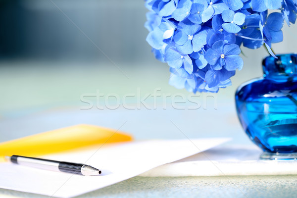 Stock photo: Blue hydrangea flower next to pen and stationery, in a calm yell