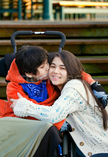 Disabled little boy kissing his big sister on cheek while seated Stock photo © jarenwicklund