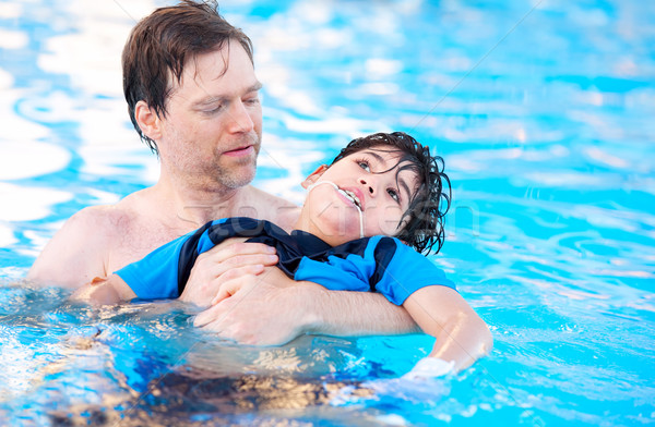 Father swimming in pool with disabled child Stock photo © jarenwicklund