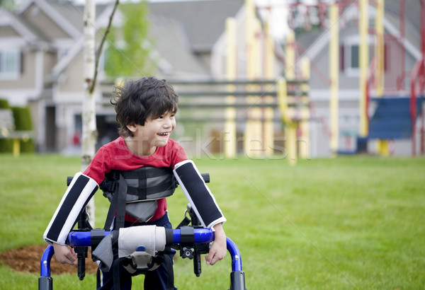 Disabled four year old boy standing in walker near a playground Stock photo © jarenwicklund