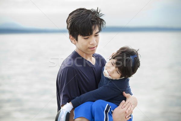 Big brother carrying disabled boy by lake shore Stock photo © jarenwicklund