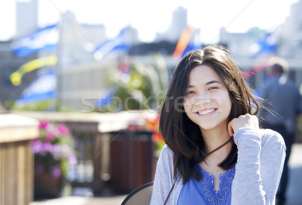 Young biracial teen girl smiling outdoors, sunny background Stock photo © jarenwicklund