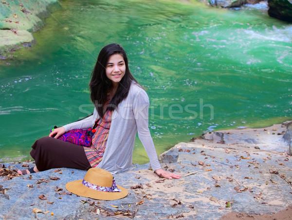 Biracial teen girl sitting next to river, smiling Stock photo © jarenwicklund