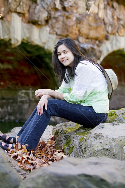 Biracial teen girl relaxing on rocks by stone bridge Stock photo © jarenwicklund