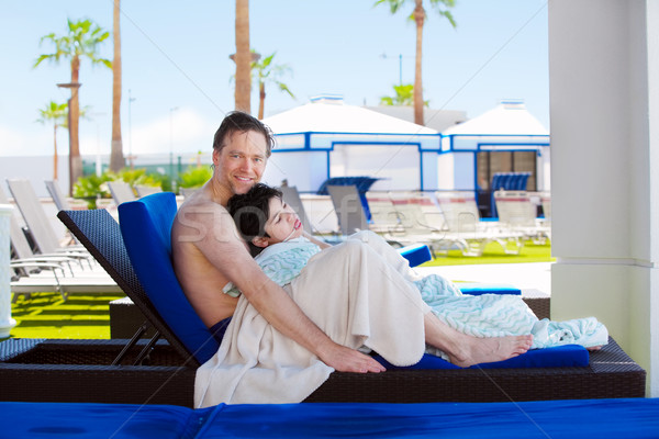 Father drying off on blue lounger with disabled son off side of  Stock photo © jarenwicklund