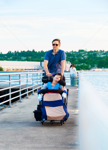 Disabled child in wheelchair outdoors by lake with family Stock photo © jarenwicklund