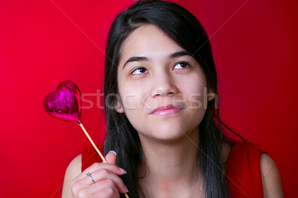 Beautiful biracial young teen girl holding heart balloon, smilin Stock photo © jarenwicklund