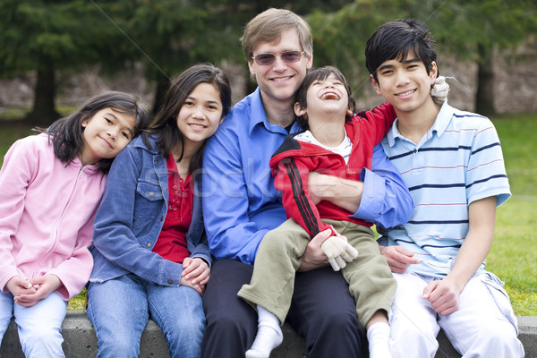 Happy interracial family enjoying day at park with disabled son Stock photo © jarenwicklund