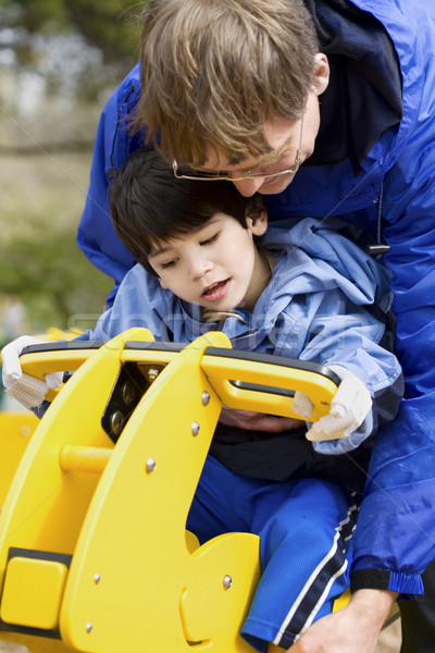 Father helping disabled son play on playground equipment Stock photo © jarenwicklund