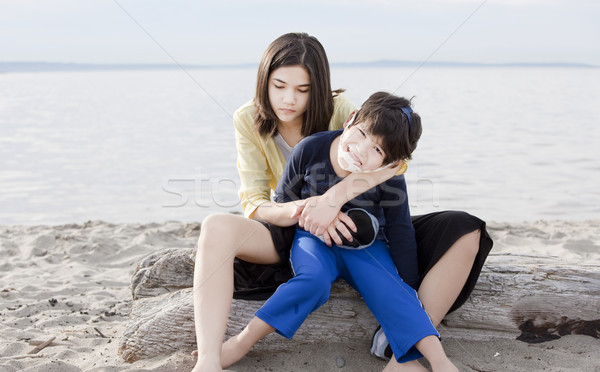 Teenage sister holding her disabled brother on the beach Stock photo © jarenwicklund
