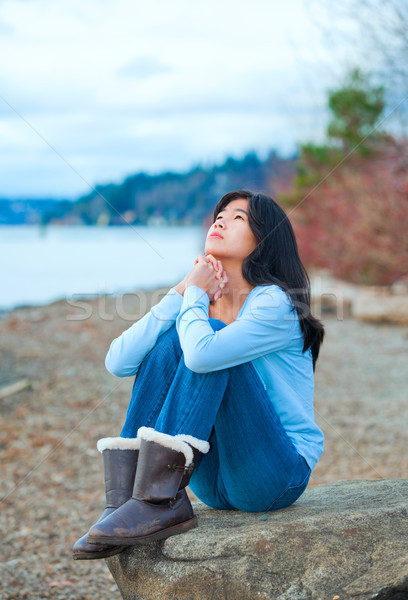 Teen girl sitting on boulder along lake shore praying Stock photo © jarenwicklund