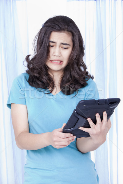 Teen girl looking with disgust at computer tablet in hand Stock photo © jarenwicklund