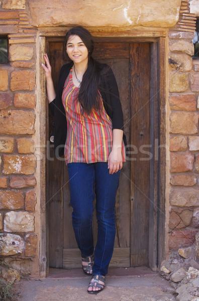 Biracial teen girl standing in brick doorway of home Stock photo © jarenwicklund