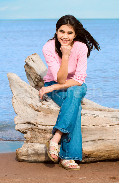Beautiful biracial teen girl sitting on fallen log by lake shore Stock photo © jarenwicklund