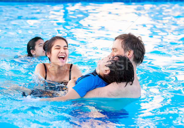 Multiracial family swimming together in pool. Disabled youngest  Stock photo © jarenwicklund