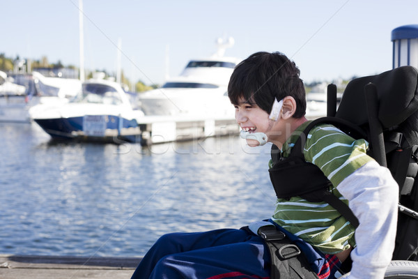 Disabled little boy in wheelchair out on pier by lake Stock photo © jarenwicklund