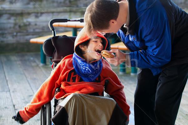 Father feeding disabled son a hamburger in wheelchair. Child has Stock photo © jarenwicklund