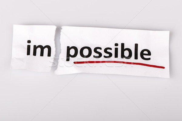 Stock photo: The word impossible changed to possible on torn paper