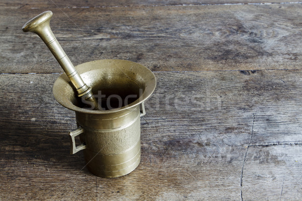 Old bronze mortar with pestle on wootden table Stock photo © jarin13