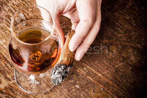 Stock photo: cigar in man hand with glass of alcohol