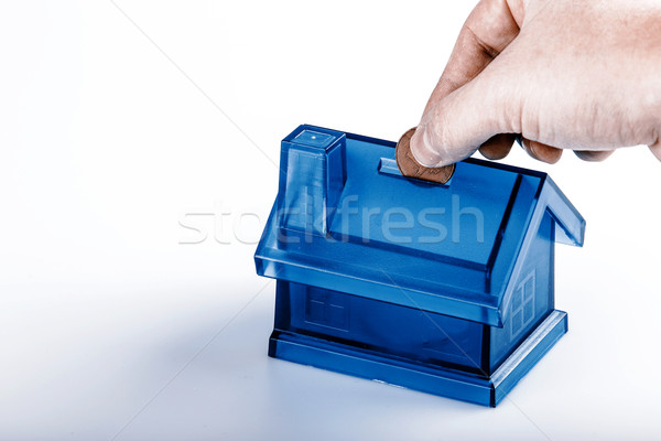 Blue House Money Box with man hand and coin on White Background Stock photo © jarin13