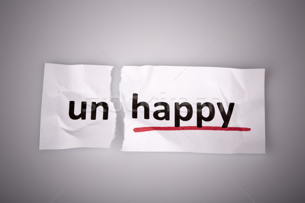 The word unhappy changed to happy on torn paper Stock photo © jarin13