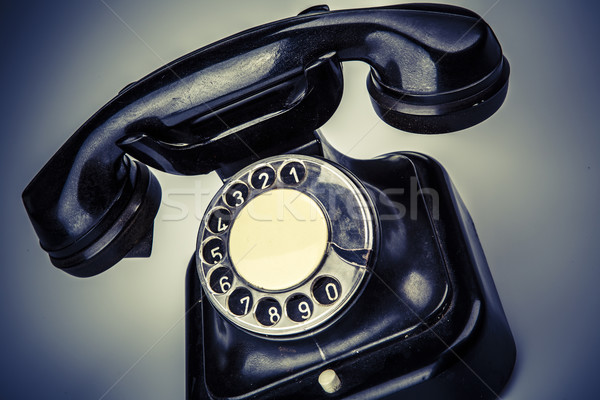 Old black phone with dust and scratches on white background Stock photo © jarin13