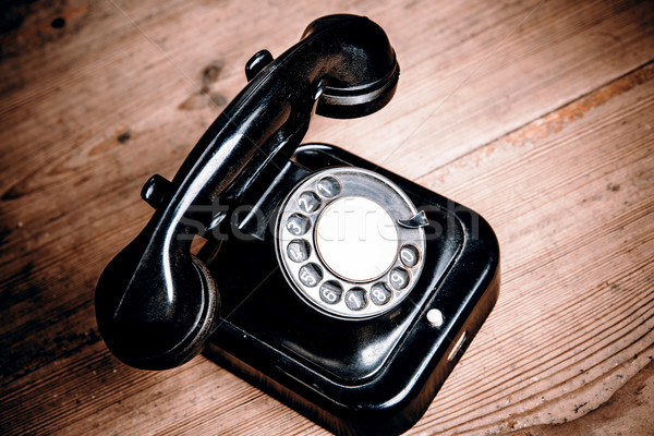 Stock photo: Old black phone with dust and scratches on wooden floor