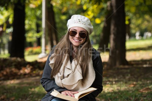 Stock fotó: Gyönyörű · fiatal · nő · olvas · könyv · park · portré