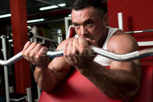 Muscular Man Exercising In Gym Stock photo © Jasminko