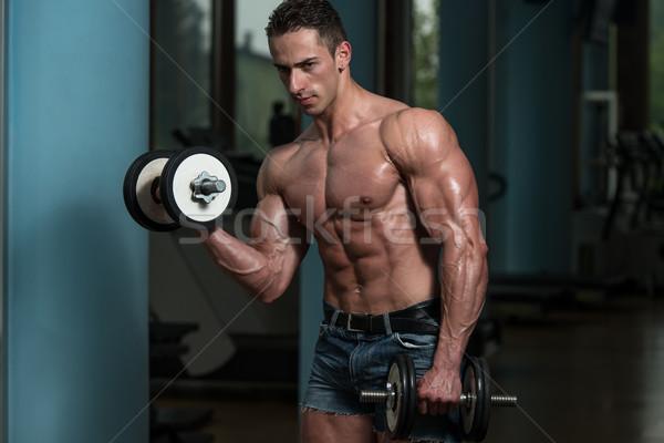 Fiatalember testmozgás súlyzók edz bicepsz súlyzó Stock fotó © Jasminko